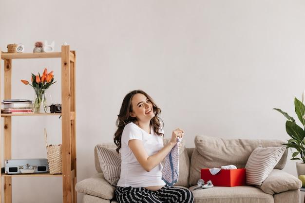 Mulher grávida alegre segurando as roupas de seu bebê