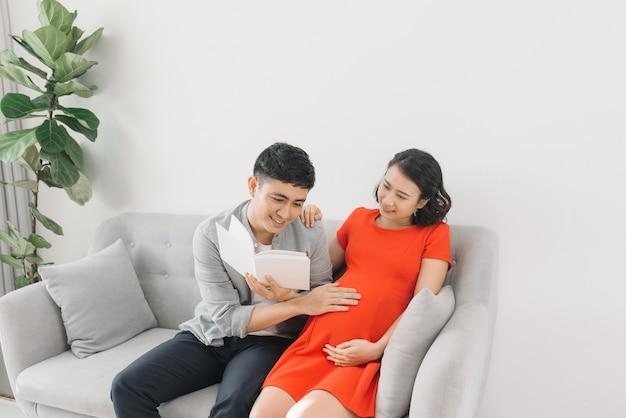 Mulher grávida asiática e marido sentado no sofá lendo livro