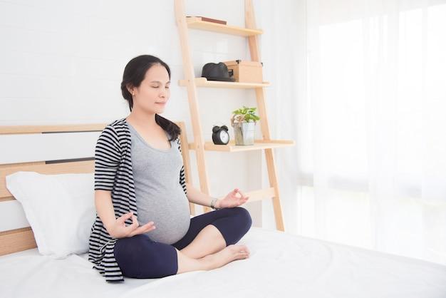 Mulher grávida asiática fazendo yoga na cama em casa