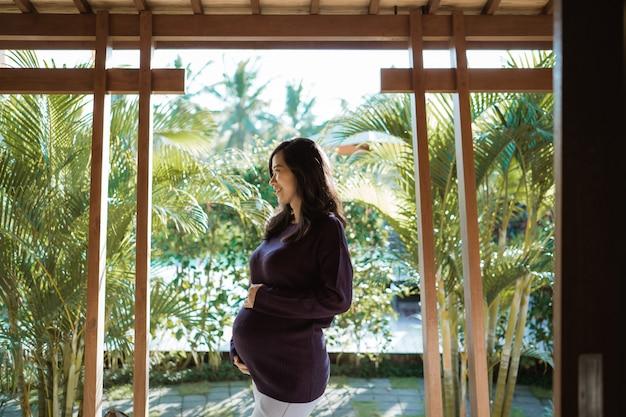 Mulher grávida asiática fica fora de casa