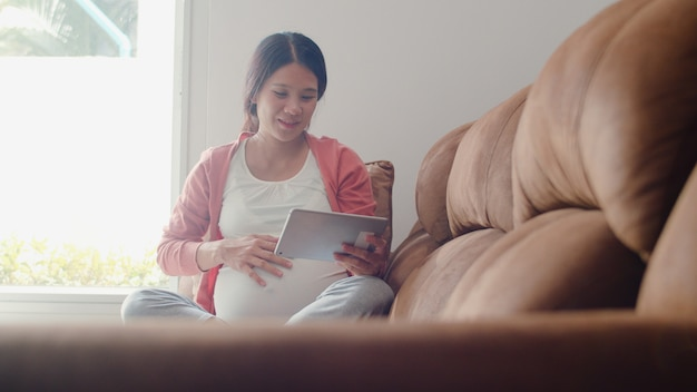 Mulher gravida asiática nova que usa a informação da gravidez da busca da tabuleta. mãe, sentindo-se feliz sorrindo positivo e pacífico enquanto cuida de seu filho deitado no sofá na sala de estar em casa.