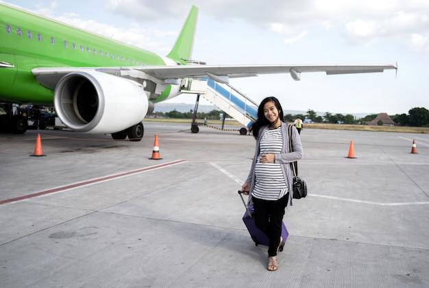 Mulher gravida asiática que está puxando a mala