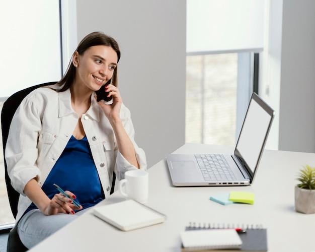 Mulher grávida atendendo uma ligação no trabalho