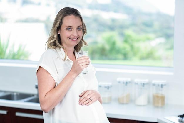 Mulher grávida, bebendo, um, vidro água, cozinha