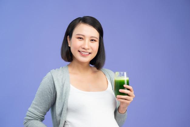 Mulher grávida bonita asiática bebendo suco verde