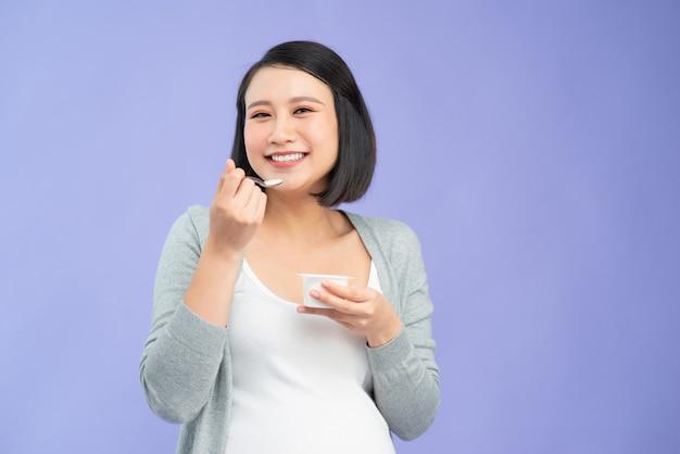 Mulher grávida bonita asiática comendo iogurte