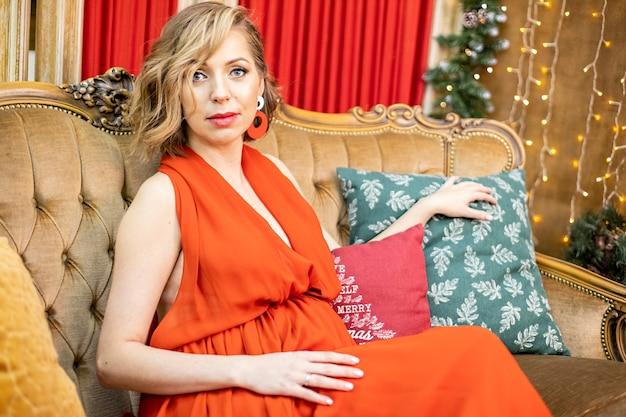 Mulher grávida bonita decorações de natal celebração família à espera de conceito de bebê
