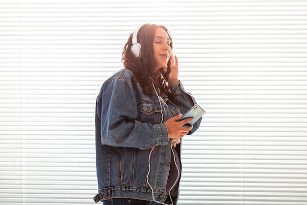 Mulher grávida bonita e pacífica ouve música clássica agradável usando smartphone e