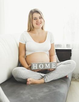 Mulher grávida bonita e sorridente segurando letras para deixar a palavra em casa