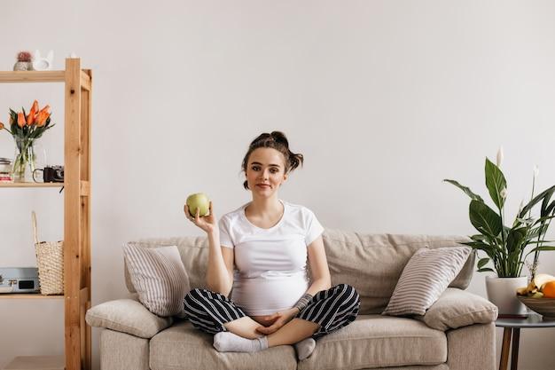 Mulher grávida bonita em uma camiseta branca e calça listrada segurando uma maçã verde