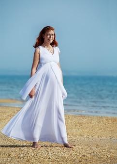 Mulher grávida bonita na praia do mar sob o céu azul