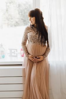 Mulher gravida bonita no vestido bege longo que está em um quarto acolhedor brilhante