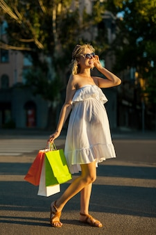 Mulher grávida bonita segurando sacolas de compras