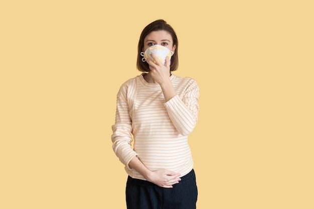 Mulher grávida, branca, usando uma máscara médica, posando em uma parede amarela