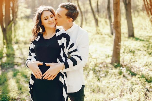 Mulher grávida brilhante e feliz andando no parque com o marido