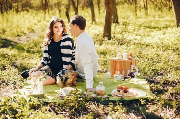 Mulher grávida brilhante e feliz sentado no parque com o marido