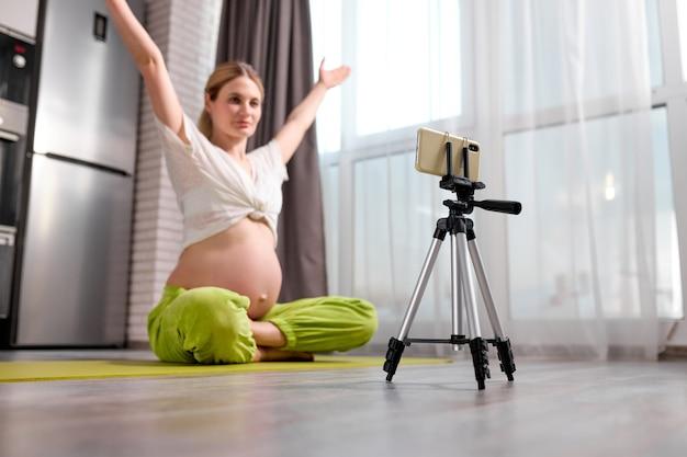 Mulher grávida calma e caucasiana sentada fazendo exercícios no chão e gravando vídeo