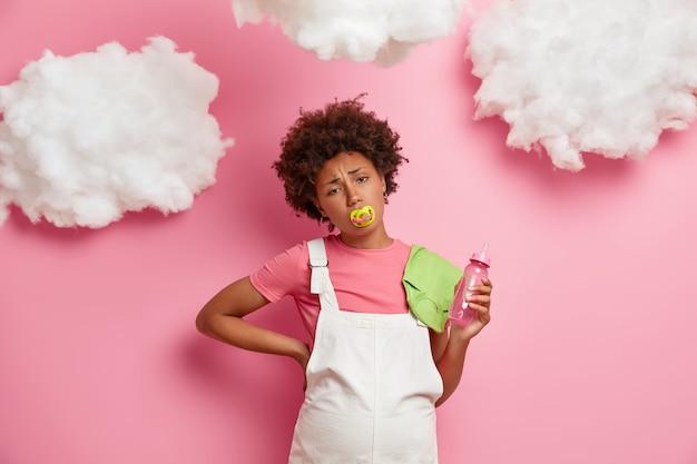 Mulher grávida cansada sofre de dor nas costas, fica com a barriga de grávida, segura itens de bebê, precisa de descanso, usa camiseta e sarafan branco, massageia as costas, isolada na parede rosa futura mãe