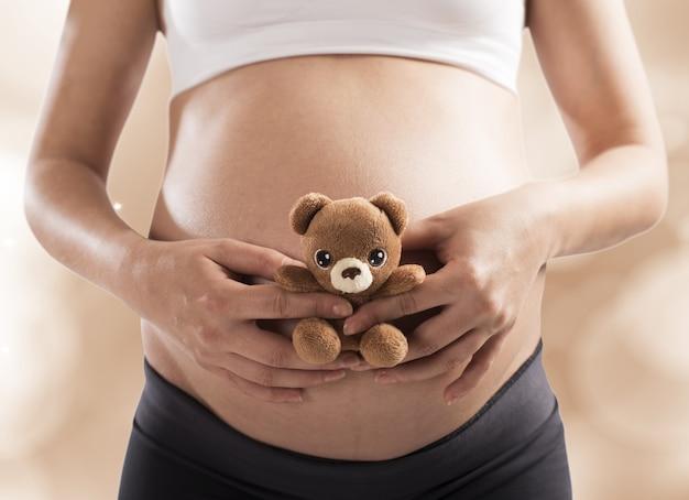 Mulher grávida carinhosa com um ursinho de pelúcia