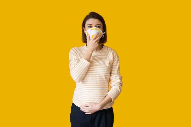 Mulher grávida caucasiana com uma máscara médica no rosto, posando em um fundo amarelo