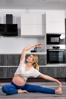 Mulher grávida caucasiana se senta no tapete de ginástica em casa fazendo exercícios para aquecer as pernas