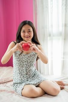 Mulher grávida chinesa segurando um coração vermelho