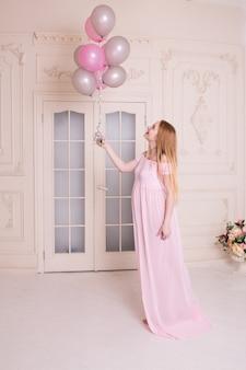 Mulher grávida com balões de ar rosa e cinza. conceito de maternidade, gravidez e expectativa.