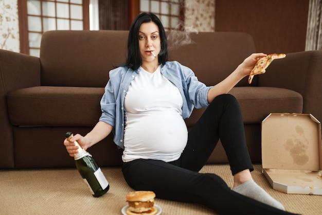 Mulher grávida com barriga fumando e bebe álcool em casa. gravidez e maus hábitos, estilo de vida pouco saudável no período pré-natal. mãe feia grávida, danos à saúde