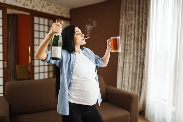 Mulher grávida com barriga fumando e bebe vinho em casa. gravidez e maus hábitos, estilo de vida pouco saudável no período pré-natal. mãe feia grávida, danos à saúde