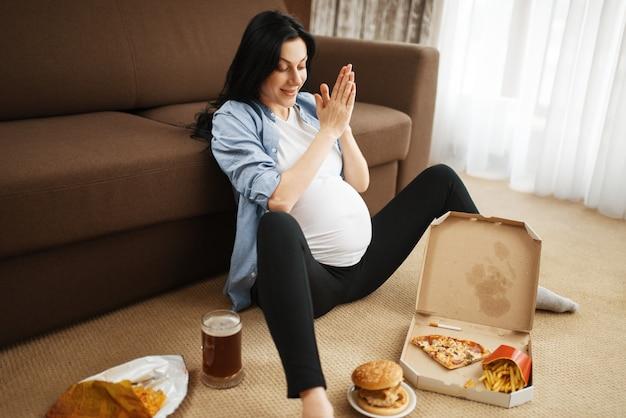Mulher grávida com barriga fumando e come alimentos pouco saudáveis em casa. gravidez, maus hábitos e estilo de vida no período pré-natal. mãe feia grávida, danos à saúde