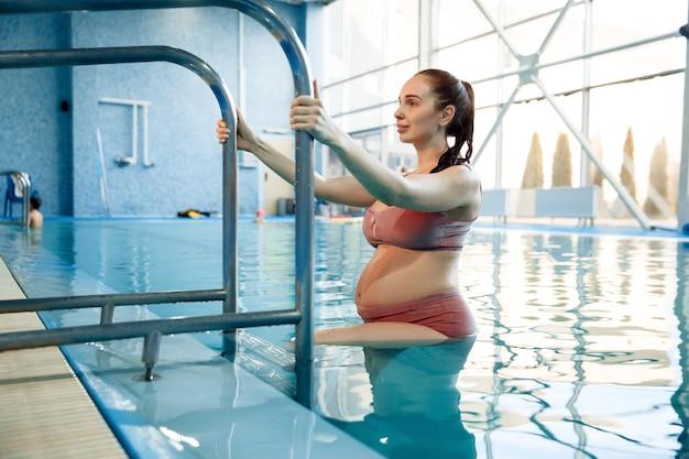 Mulher grávida com barriga grande sobe uma escada fora da água na piscina dentro de casa
