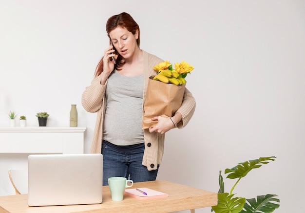 Mulher grávida com buquê de flores falando por telefone