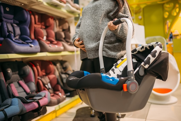 Mulher grávida com cama portátil, escolhendo a cadeirinha infantil na loja. bens para o transporte seguro de crianças