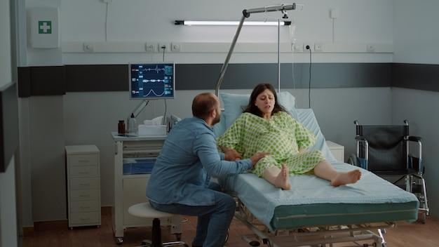 Mulher grávida com contrações dolorosas na enfermaria do hospital
