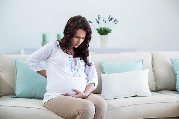 Mulher grávida, com, doloroso, costas, em, sala de estar