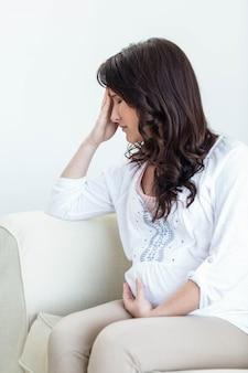 Mulher grávida, com, dor de cabeça, sentar sofá