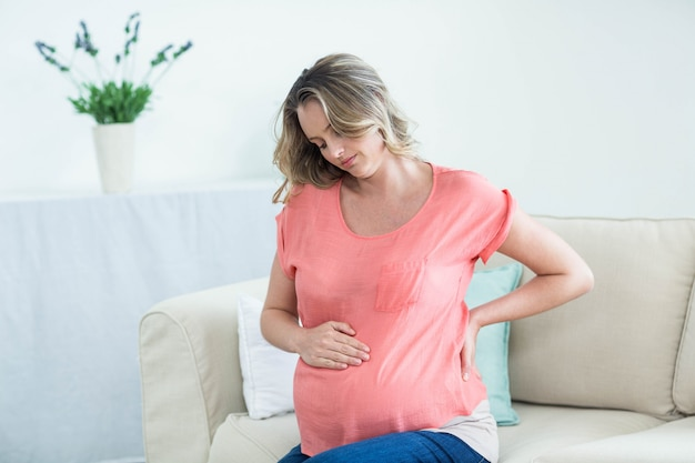 Mulher grávida, com, dor traseira, em, a, sala de estar