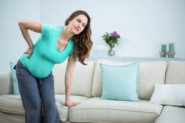 Mulher grávida, com, dor traseira, em, sala de estar