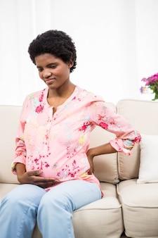 Mulher grávida, com, dor traseira, ligado, sofá