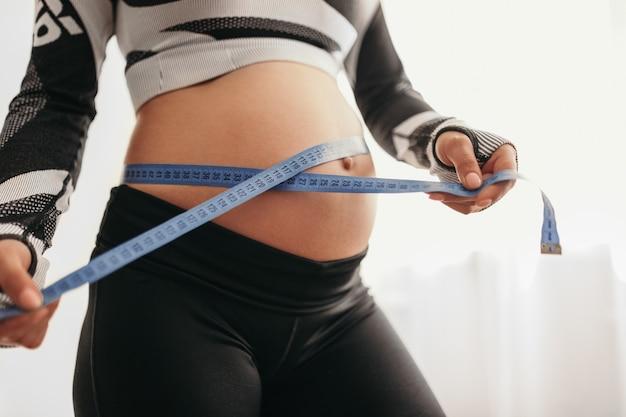 Mulher grávida com fita métrica