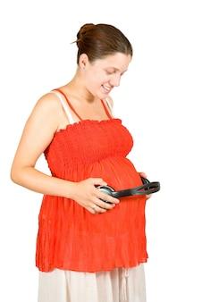 Mulher grávida com fones de ouvido na barriga