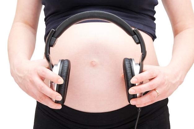 Mulher gravida com fones de ouvido