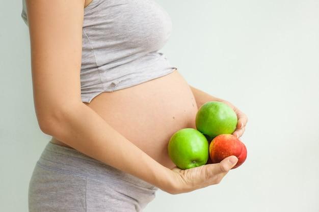 Mulher grávida com frutas nas mãos dela