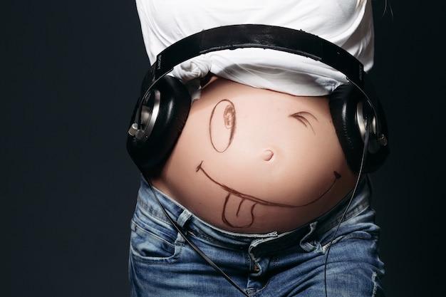 Mulher grávida com grandes fones de ouvido na barriga.