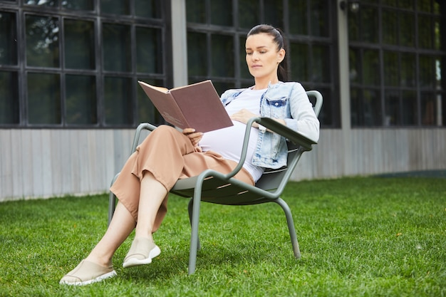 Mulher gravida com livro que aprecia o verão