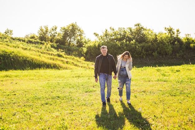 Mulher grávida com marido caminhando na natureza