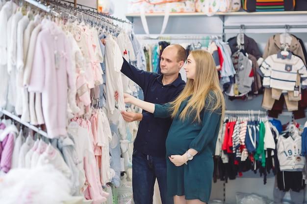 Mulher gravida com marido comprando bebê.