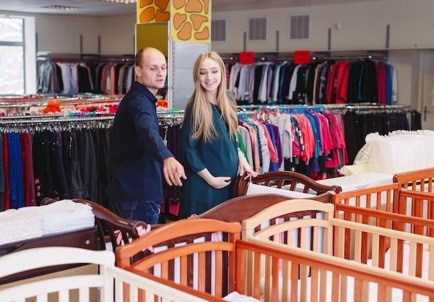 Mulher grávida com o marido escolhe um berço na loja.