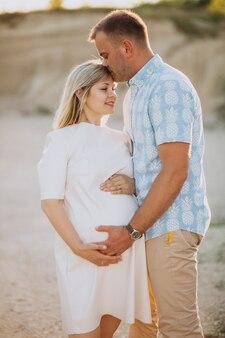 Mulher grávida com o marido na pedreira de areia