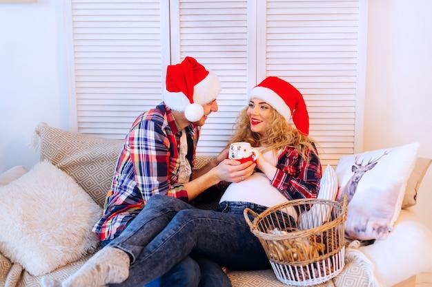 Mulher grávida com o marido no sofá entre almofadas no ano novo